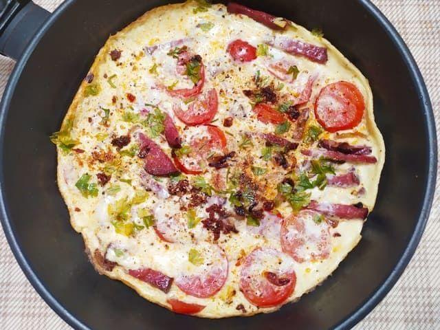 Омлет с колбасой и помидорами на сковороде