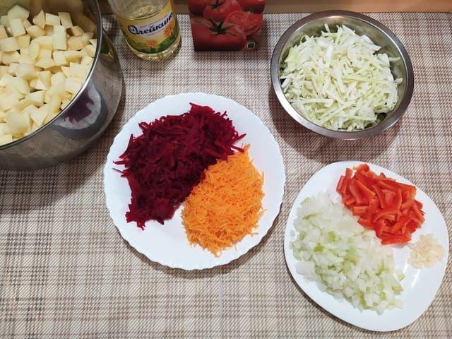 Овощи для борща: тертая свекла и морковь, нарезанный картофель, капуста в миске, лук, перец и чеснок