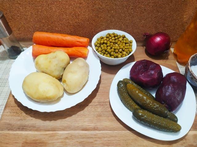 Ингредиенты для винегрета: вареная картошка и морковка, отваренная свекла и соленые огурцы на тарелке, зеленый горошек в миске