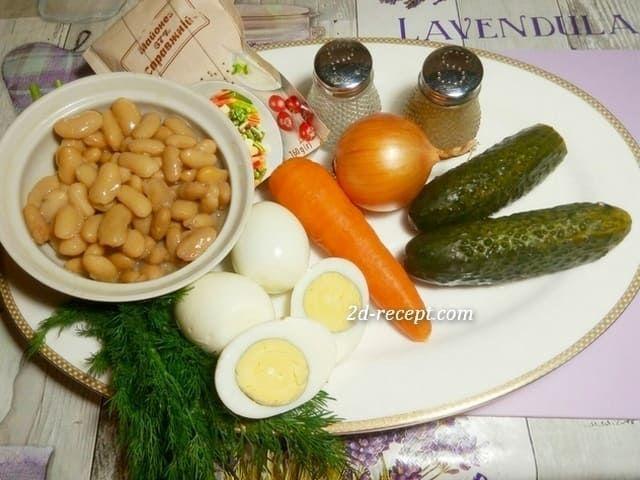 Ингредиенты для салата: консервированная фасоль белая, 1 отваренная морковь и 3 яйца, лук, 2 соленых огурца, майонез, соль, перец и зелень
