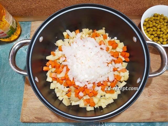 Нарезанный лук, морковь и картофель в кастрюле