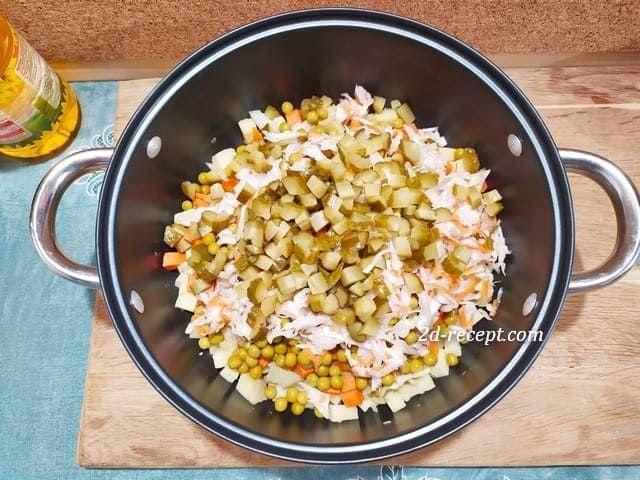 Нарезанные огурцы с овощами для винегрета в кастрюле