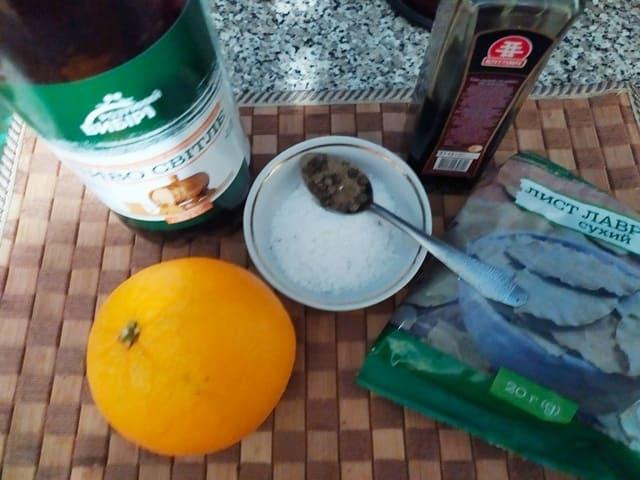 Ингредиенты для маринада для утки: пиво, апельсин, соевый соус, лавровый лист в упаковке, соль и перец горошком на ложке