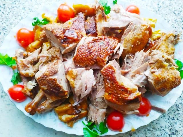 Нарезанная кусками запеченная утка с яблоками на тарелке с помидорами-сливками и зеленью