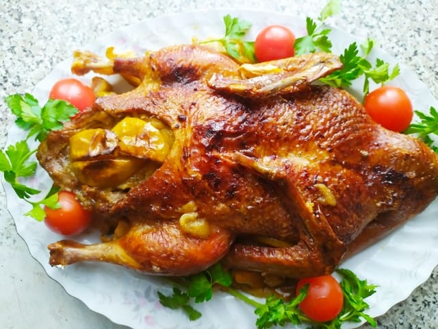 Запеченная утка, фаршированная яблоками, на тарелке со сливовыми помидорами и зеленью петрушки