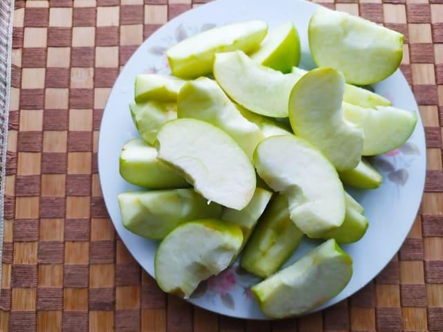 Яблоки для утки нарезанные кусочками на сервировочной тарелке